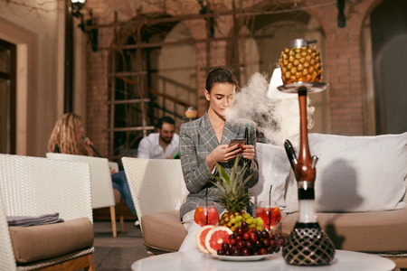 Woman With Phone Smoking Fruit Hookah In Shisha Bar. Girl Relaxing With Shisha. High Resolution