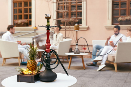 Shisha With Fruits On Table In Hookah Bar Closeup. People Smoking And Relaxing On Background. High Resolution
