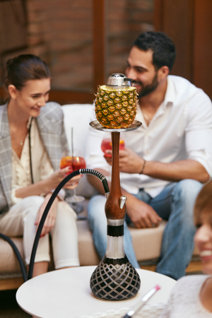 Couple Smoking Shisha With Fruit Cup In Hookah Bar. Man And Woman Smoke Hookah, Drinking Cocktails In Cafe. High Resolution