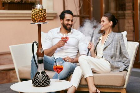 Paar Rauchen Shisha Mit Obstschale In Der Shisha-Bar. Mann und Frau rauchen Wasserpfeife, trinken Cocktails im Café. Hohe Auflösung