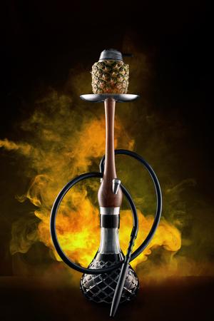 Shisha mit Obstschale mit buntem Rauch in der Shisha-Bar-Nahaufnahme. Ananas Shisha Mit Gelbem Rauch Auf Schwarzem Hintergrund. Hohe Auflösung Standard-Bild