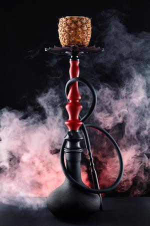 Shisha With Fruit Bowl With Colorful Smoke In Hookah Bar Closeup. Pineapple Shisha With Red Smoke On Black Background. High Resolution