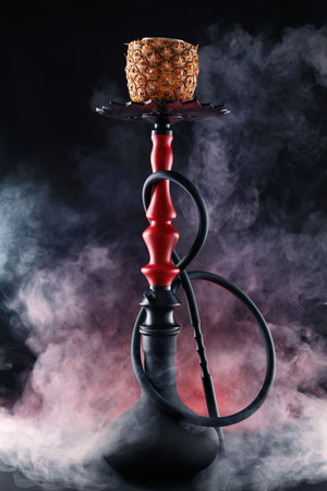 Shisha With Fruit Bowl With Colorful Smoke In Hookah Bar Closeup. Pineapple Shisha With Red Smoke On Black Background. High Resolution