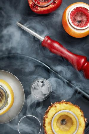 Hookah Shisha With Smoke And Fruit Bowl Background. Shisha Equipment On Black Table. High Resolution