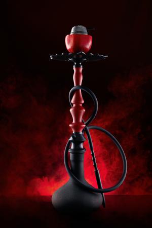 Granatapfel-Shisha mit rotem Rauch auf schwarzem Hintergrund. Standard-Bild