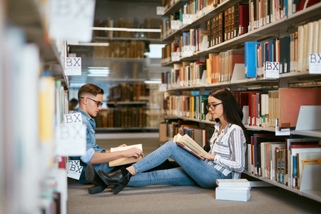 Students Studying In University Library. Man And Woman Reading Books Sitting On Floor Between Bookshelves. High Resolution