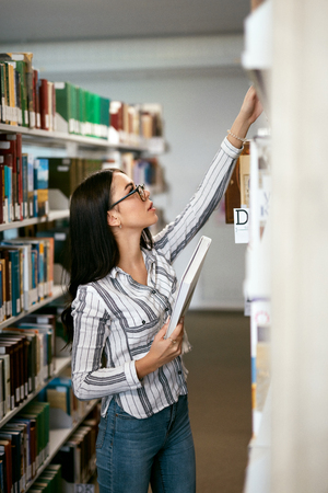 Student Woman Searching Books In Bookstore Or Library. Woman Searching For Textbook  On Bookshelves. High Resolution