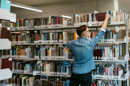 Man Looking For Book In Bookstore. Student In Library Trying To Find Textbook On Bookshelves. High Resolution