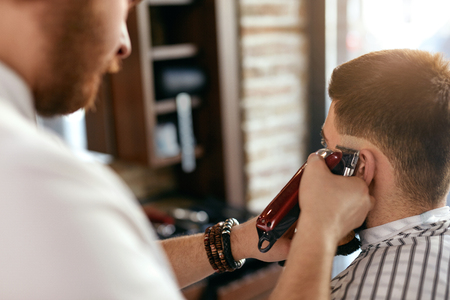 Men Hair Cut In Barber Shop. Close Up Of Hairdresser Cutting Mans Hair With Trimmer. High Resolution