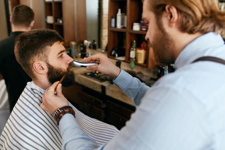 Barber Shop. Man Gets Beard Hair Cut. Barber Trimming Mans Beard With Trimmer In Men Hair Salon. High Resolution Stock fotó