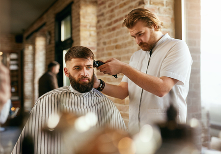 Barber Shop. Man Getting Haircut In Hair Salon. Hairdresser Cutting Hair With Trimmer, Doing Hairstyle. High Resolution Stock Photo