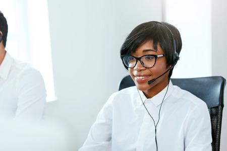 Agent de centre d'appels travaillant sur la hotline. Jolie femme afro-américaine au service des clients dans le centre de contact. Haute résolution Banque d'images