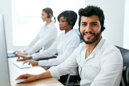 Call Center Operator With Colleagues At Workplace. Man Serving Customers On Hotline. High Resolution