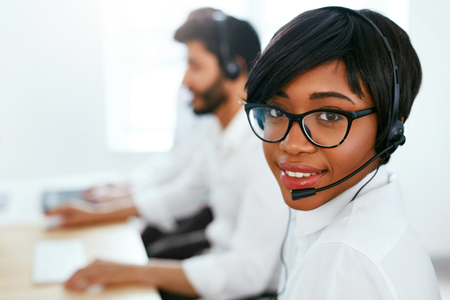 Call Center Agent Working On Hotline. Attractive Afro-American Woman Serving Customers In Contact Center. High Resolution Stok Fotoğraf - 105984303