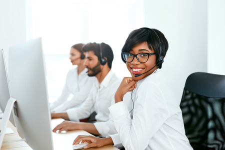 Call Center Operator With Colleagues At Workplace. Woman Serving Customers On Hotline. High Resolution