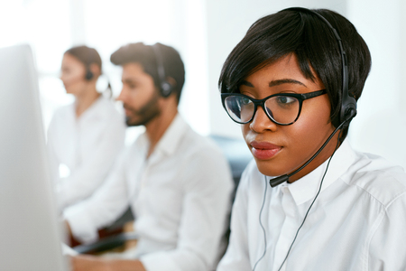 Call Center Agent Working On Hotline. Attractive Afro-American Woman Serving Customers In Contact Center. High Resolution