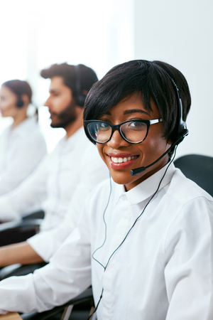 Call Center Agent Working On Hotline. Attractive Afro-American Woman Serving Customers In Contact Center. High Resolution Stok Fotoğraf - 105455327