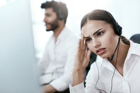 Tired Call Center Operator At Workplace. Woman With Headache Working On Helpline. High Resolution Stok Fotoğraf