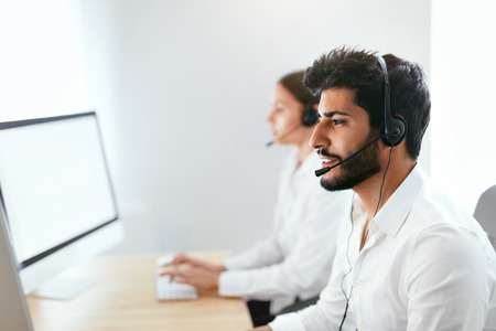 Contact Center Agent Consulting Customers Online. Man And Woman Working On Helpline In Call-Center. High Resolution