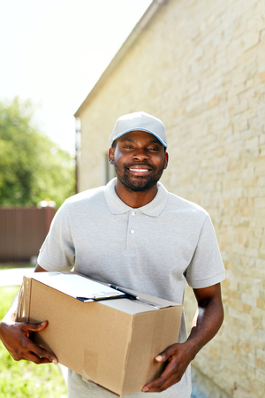 Delivery Man. Portrait Of Smiling Courier With Box Package