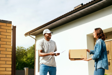 Courier Delivery. Man Delivering Package To Woman At Home