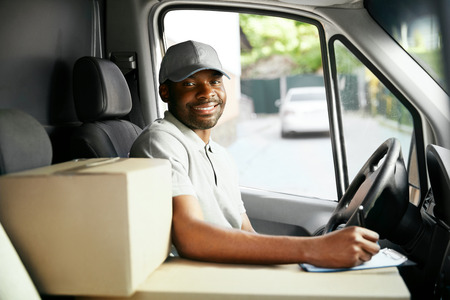 Dostawa kurierska. Czarny kierowca jazdy samochodem dostawczym