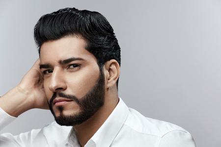Mode-Mann-Porträt. Männliches Modell mit Frisur und Bart