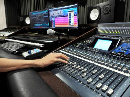 Studio nagrań dźwiękowych z profesjonalnym sprzętem do nagrywania muzyki, panelem sterowania miksera i monitorami komputerowymi. Wysoka rozdzielczość