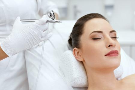 Cuidado de la piel facial de belleza. Mujer recibiendo tratamiento con spray de oxígeno en la piel facial en la clínica de cosmetología Closeup. Alta resolución