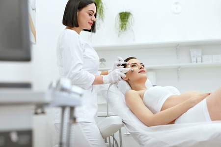 Beauty Treatment. Pregnant Woman Getting Cryo Oxygen Therapy On Facial Skin At Cosmetology Clinic. High Resolution