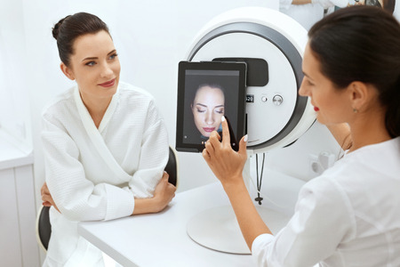 Face Skin Analyze. Cosmetologist Analyzing Woman Facial Skin At Cosmetology Clinic. High Resolution