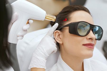 Cosmetología. Mujer en tratamiento de estimulación láser de crecimiento del cabello en la clínica de belleza médica. Alta resolución