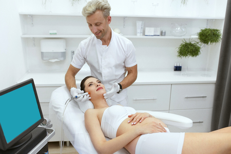 Pregnant Woman Getting Facial Beauty Treatment At Cosmetology Clinic. Cosmetologist Doing Acne Scars Skin Dermabrasion Therapy. High Resolution Stock Photo