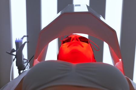 Cosmetology. Woman Face Getting Red Light Oxygen Treatment At Beauty Clinic. Facial Photo Therapy. High Resolution