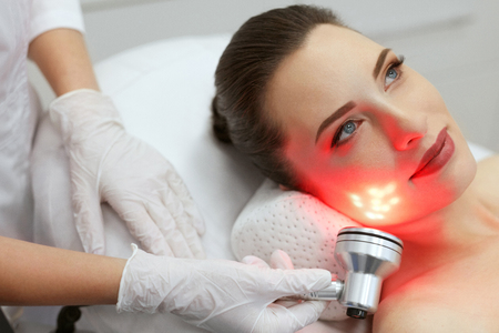Red Led Light Treatment. Woman Doing Facial Skin Therapy At Cosmetology Beauty Clinic. High Resolution Standard-Bild - 108157997
