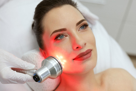 Facial Beauty Treatment. Woman Doing Red Led Light Therapy On Face Skin At Cosmetology Center. High Resolution