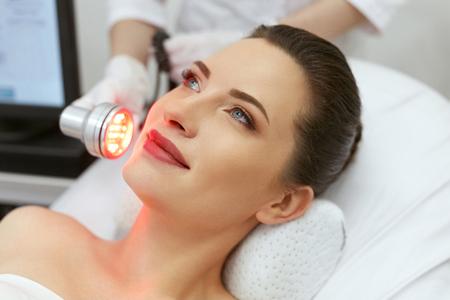Cosmetología. Mujer en terapia de luz roja LED facial en la clínica. Cosmetóloga con luz roja para el tratamiento de la piel. Alta resolución Foto de archivo