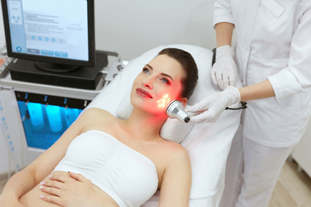 Red Led Light Treatment. Woman Doing Facial Skin Therapy At Cosmetology Beauty Clinic. High Resolution