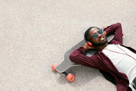 Man Listening Music In Headphones On Street, Relaxing On Longboard. High Resolution Stock Photo