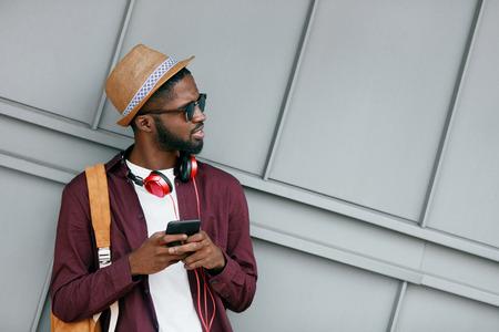 Bel homme noir en vêtements de mode avec téléphone dans la rue. Homme africain élégant avec casque et téléphone en ville. Haute résolution