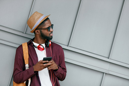 Handsome Black Man In Fashion Clothes With Phone On Street. Stylish African Man WIth Headphones And Phone In City. High Resolution