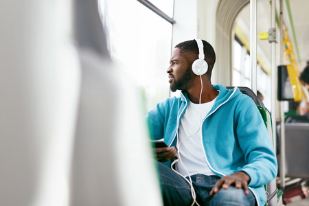 Man Riding Bus, Listening Music With Headphones And Phone In Public Transport. Handsome African Male With Earphones. High Resolution