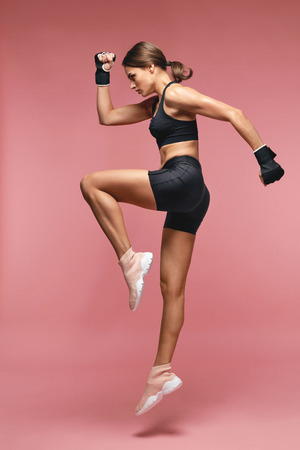 Jump. Sport Woman In Sportswear Jumping On Pink Background, Female Athlete In Jump Motion. High Resolution