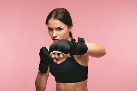 Boxeadora. Entrenamiento de deportista en vendas de boxeo, posando sobre fondo rosa. Alta resolución