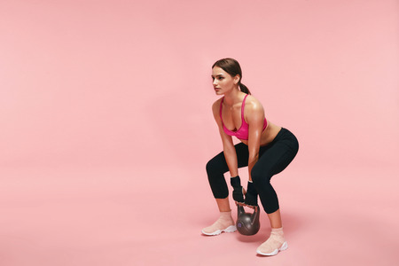 Sport Training. Athletic Woman Doing Squats With Dumbbell On Pink Background. High Resolution