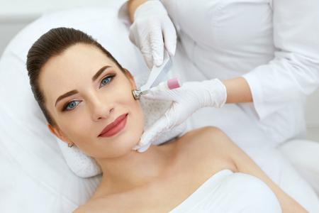 Klinika Urody. Kobieta wykonująca zabieg kriotlenowy na twarz