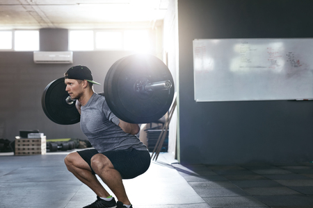 Workout At Gym. Sports Man Doing Squats With Barbell Row, Male Athlete Training Squat. High Resolution Reklamní fotografie