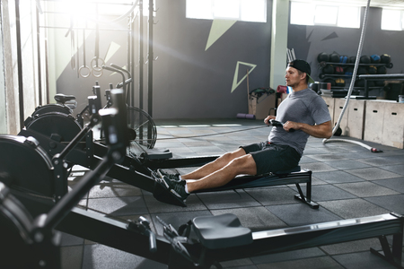 Functional Training. Man Doing Exercise On Rowing Machine At Gym, Sport Male Athlete Workout. High Resolution