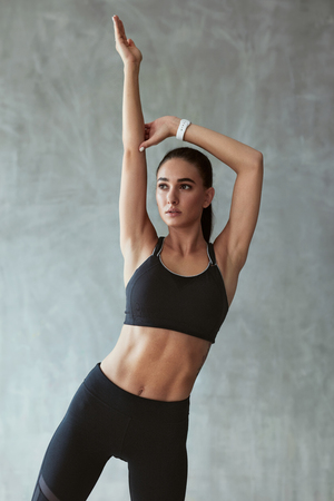 Stretch. Sports Woman Stretching In Fashion Black Sport Clothes On Grey Background. High Resolution