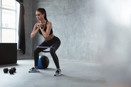 Squats. Sports Woman In Fashion Clothes Squatting With Resistance Band, Exercising Home. High Resolution